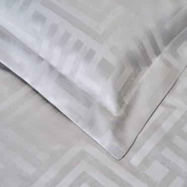 Выверенный орнамент из пересекающихся линий был вдохновлён античным мотивом — меандром. Его непрерывность — это символ непрерывности движения, из которого состоит наша жизнь. Для тех, кто всегда готов сделать шаг вперёд.  Соткан из предварительно окрашенных волокон хлопка фактурный жаккард плотностью 500 нитей на квадратный дюйм (500 TC).